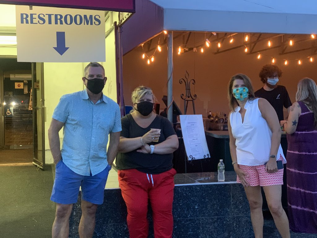 People wear masks while standing outside the snack bar at a drive in movie theater.