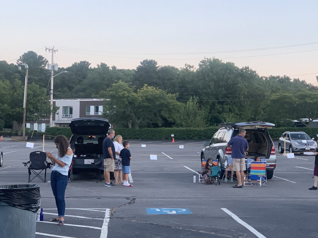 Families social distance at an outdoor drive in movie theater.