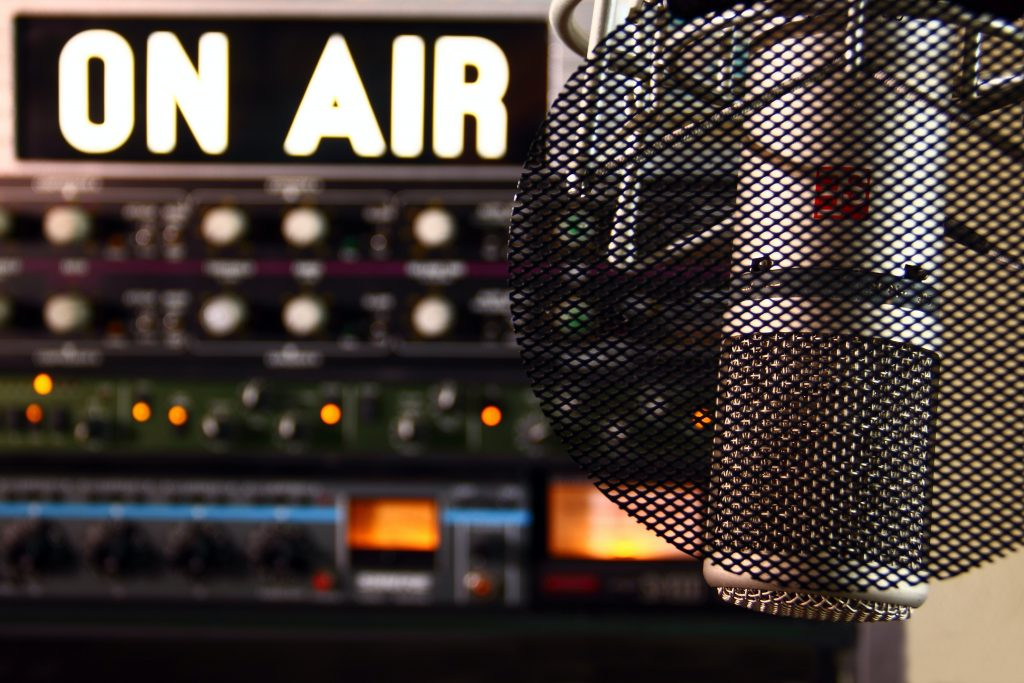 "a microphone and a sign which reads ""on air"" in a recording studio"