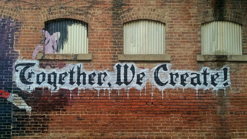"Graffiti mural reading ""Together, We Create!"""
